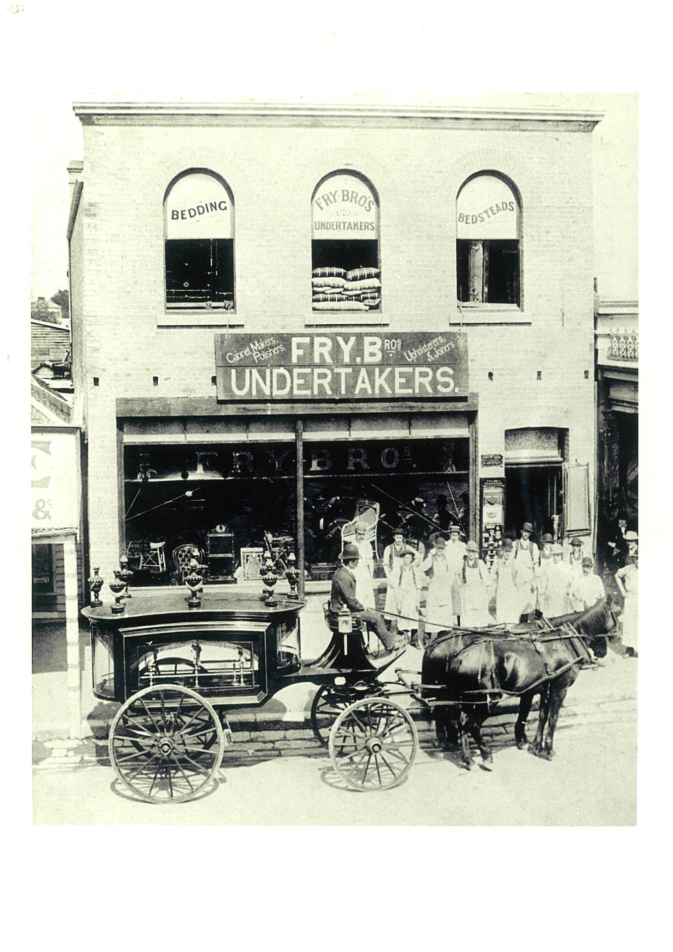 Photograph of fry bros funeral home in maitland 1889 upfront by people and cart funeral vehicle.