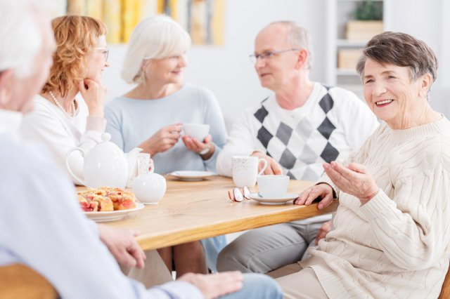 Group of middle age people having breakfast and tea together