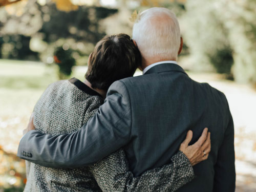 Older couple with their backs to the camera with their arms around eachother