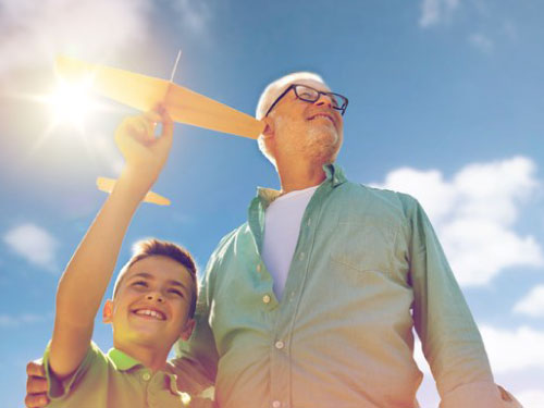 Grandfather and Grandson together. Grandson holding a wooden airplane in his hand