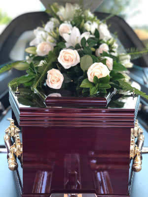 Rosewood coffin decorated with flowers at a funeral